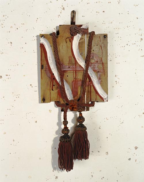 Objet sans titre, couvercle de boîte de munitions peint, cordelière@et deux pompons (70 x 33 cm)