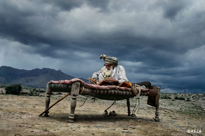 Afghanistan. April 1983. An old man sitting on a bench is reading Koran near the Pakistani border. He is a refugee fleeing the Soviet invasion with his family. Afghanistan. Avril 1983. Un vieil homme assis sur un banc lit le coran, près de la frontière pakistanaise. C'est un réfugié, fuyant l'invasion soviétique avec sa famille.